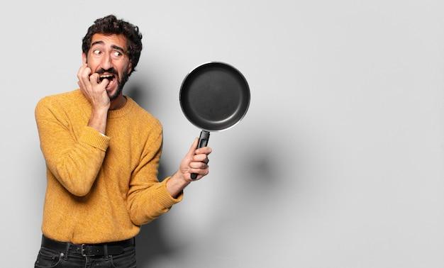 냄비와 젊은 미친 수염 된 남자. 요리 개념