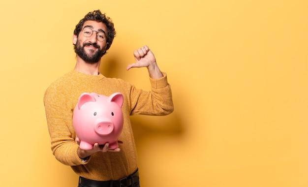 貯金箱を持つ若い狂ったひげを生やした男 Premium写真