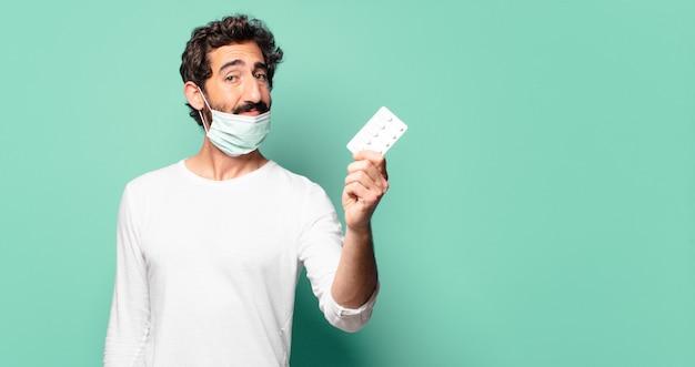 Молодой сумасшедший бородатый мужчина с таблеткой таблеток