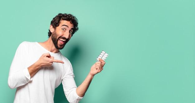 錠剤タブレットを持つ若い狂ったひげを生やした男