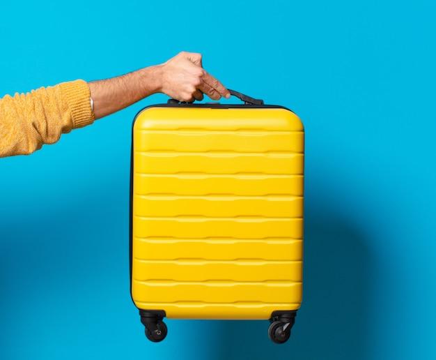 Молодой сумасшедший бородатый мужчина с чемоданом