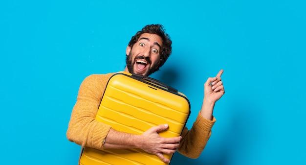 スーツケースを持つ若い狂気のひげを生やした男