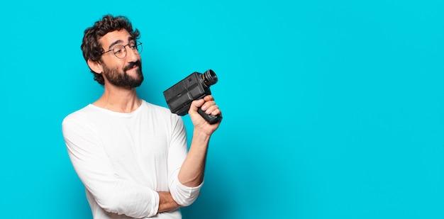 スーパー 8 カメラを持つ若い狂気のひげを生やした男
