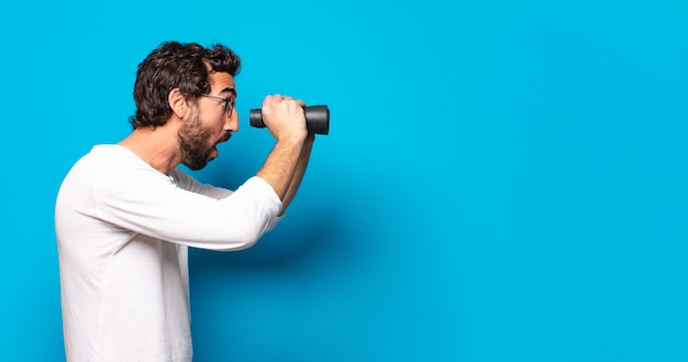 Young crazy bearded man with binoculars