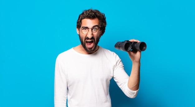쌍안경으로 젊은 미친 수염된 남자