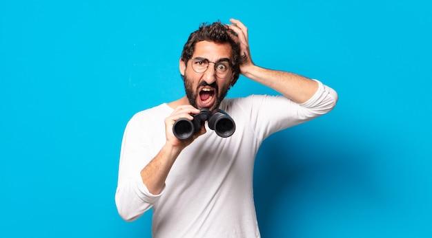 双眼鏡で若い狂ったひげを生やした男