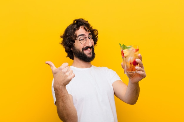 Young crazy bearded man with a cocktail. tourist concept