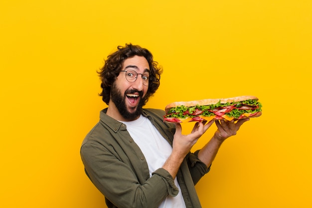 Young crazy bearded man with a giant sandwich.