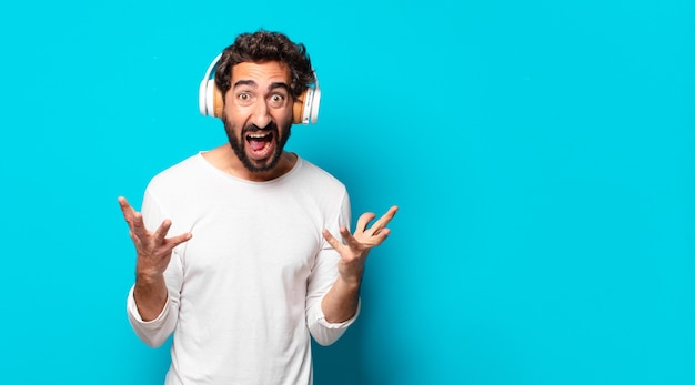 Young crazy bearded man with headphones listening music