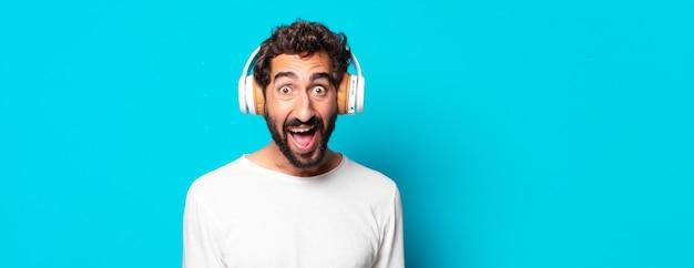 헤드폰 음악 듣기와 젊은 미친 수염 된 남자