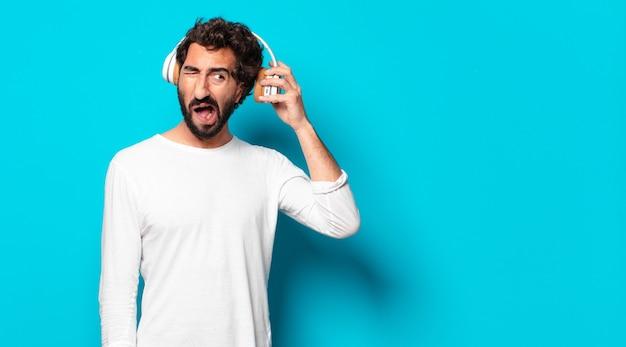 Молодой сумасшедший бородатый мужчина в наушниках слушает музыку