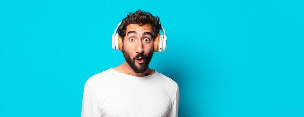 音楽を聴いているヘッドフォンを持つ若い狂ったひげを生やした男