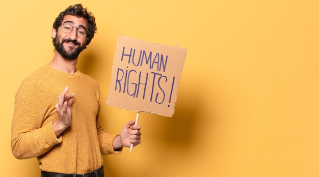 Young crazy bearded man with a human rights cardboard.
