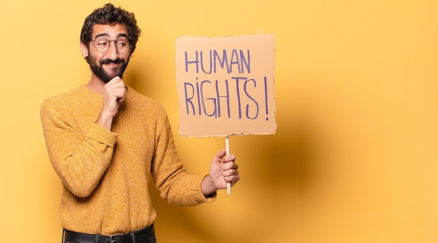 Young crazy bearded man with a human rights cardboard