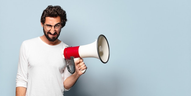 Young crazy bearded man with a megaphone