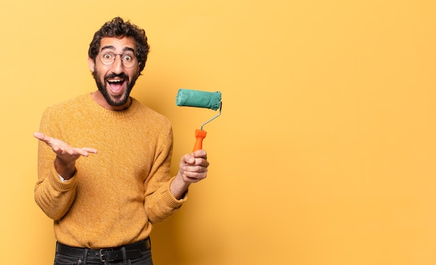 Young crazy bearded man with a paint roller painting and changing the wall color