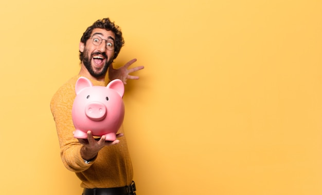 Young crazy bearded man with a piggy bank