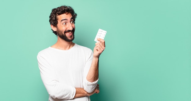 Young crazy bearded man with a pills tablet