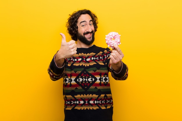 Young crazy bearded man with a sugar donut
