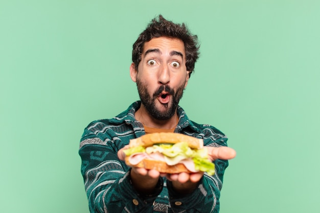 Young crazy bearded man with surprised expression and holding a sandwich