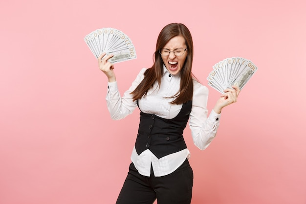 Young crazy business woman in glasses screaming hold bundle lots of dollars, cash money spreading hands isolated on pink background. lady boss. achievement career wealth. copy space for advertisement.
