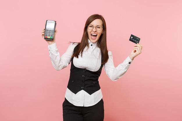 미친 비즈니스 여성은 분홍색 배경에 격리된 검정색 카드인 신용 카드 결제를 처리하고 획득하기 위해 무선 현대적인 은행 결제 단말기를 들고 비명을 질렀습니다. 여사장님. 성취 경력 부입니다.