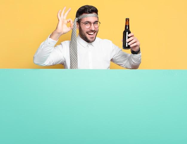 Молодой сумасшедший бизнесмен с бутылкой пива празднует хорошие новости