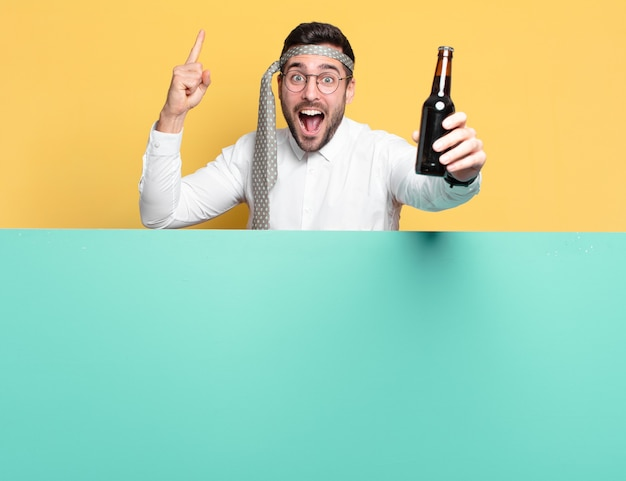 Young crazy businessman with a beer bottle celebrating good news