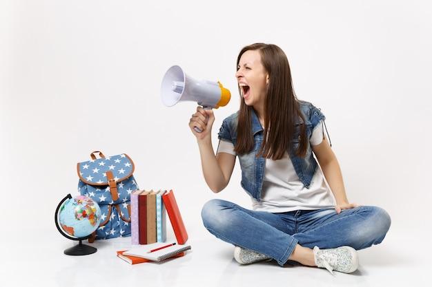 Giovane studentessa casuale pazza in vestiti di denim che urla tenendo il megafono seduto vicino al libro di scuola dello zaino del globo isolato
