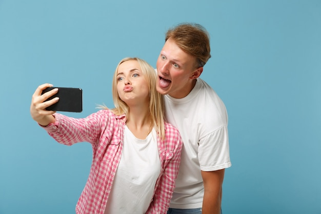 Young crazy cheerful couple friends man and woman  in white pink empty t-shirts posing