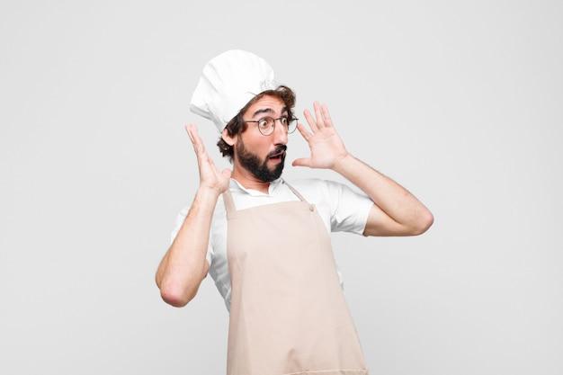 Молодой сумасшедший шеф-повар с открытым ртом, в ужасе и шоке от ужасной ошибки, поднимает руки к белой стене