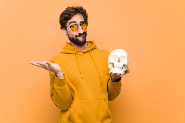 オレンジ色の壁に対して人間の頭蓋骨モデルを保持している若いクレイジークール