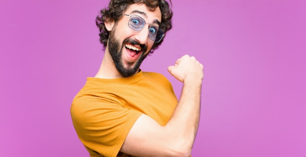Молодой сумасшедший спокойный человек, чувствующий себя счастливым, позитивным и успешным, мотивированный, когда сталкивается с проблемой или празднует хорошие результаты на фоне плоской стены