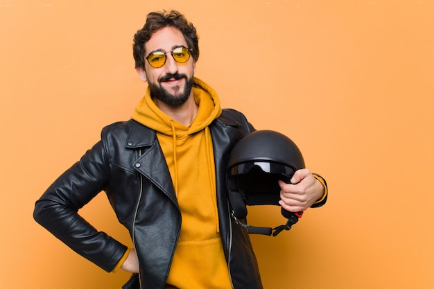 Young crazy cool man rider, holding a motorbike helmet.