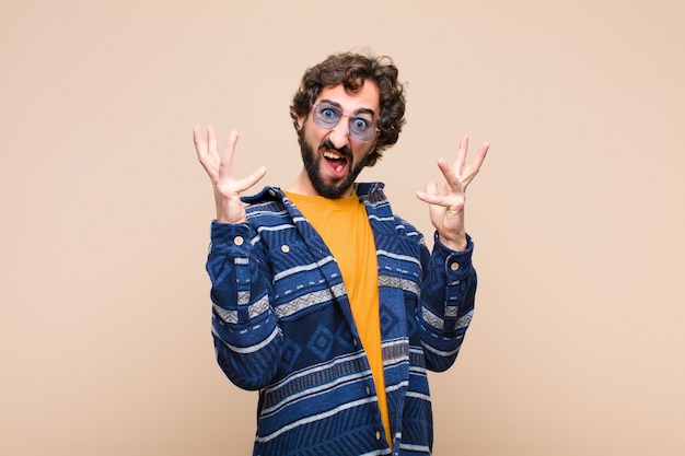 Young crazy cool man screaming with hands up in the air, feeling furious, frustrated, stressed and upset against flat wall