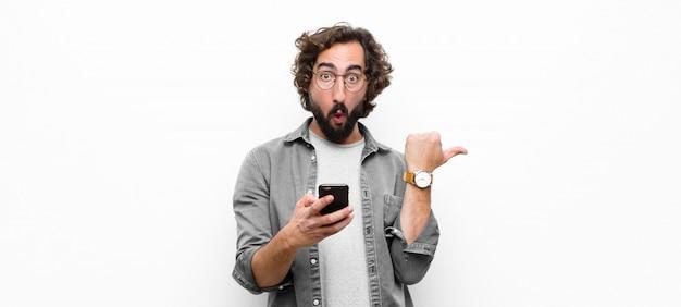 Молодой сумасшедший крутой человек, используя свой смартфон на белой стене