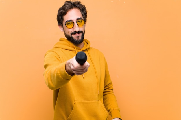 Молодой сумасшедший крутой человек с микрофоном на оранжевой стене