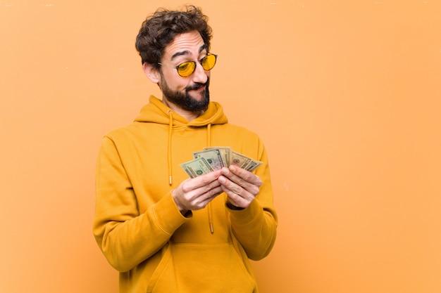 Молодой сумасшедший крутой человек с долларовых банкнот на оранжевой стене