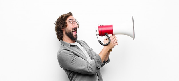 Young crazy cool man with a megaphone against white wall