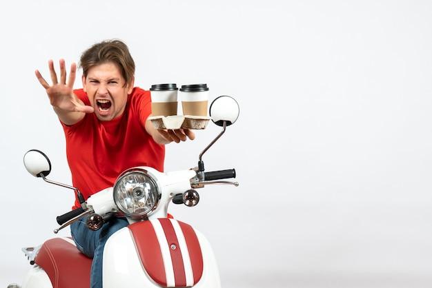 Ragazzo giovane corriere emotivo pazzo in uniforme rossa che si siede sul motorino che tiene gli ordini che mostrano cinque sulla parete gialla