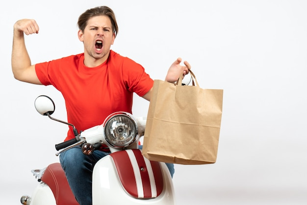 Young crazy emotional courier guy in red uniform sitting on scooter holding paper bag showing his muscular on white wall