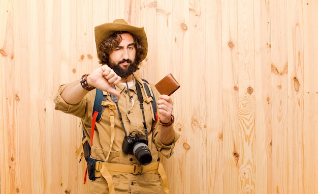 Young crazy explorer with straw hat and backpack on wood background