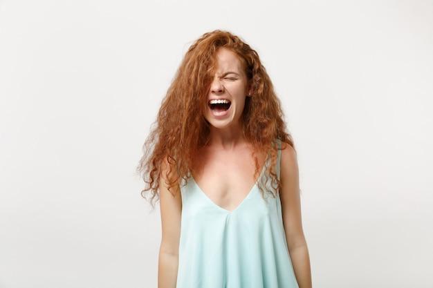 흰색 벽 배경에 격리된 채 캐주얼한 가벼운 옷을 입은 젊은 미친 좌절된 빨간 머리 여성. 사람들은 진심 어린 감정 라이프 스타일 개념입니다. 복사 공간을 비웃습니다. 비명을 지르며 눈을 감고 있습니다.