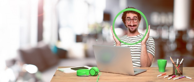 Young crazy graphic designer on a desk with a laptop