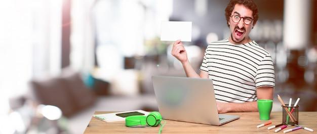Молодой сумасшедший графический дизайнер на столе с ноутбуком