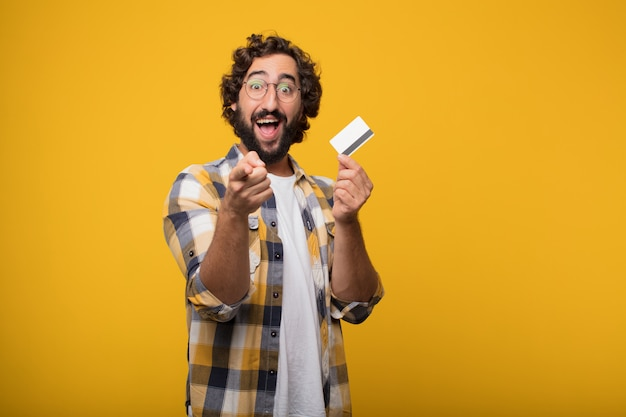 Young crazy mad man  fool pose with a credit card. cash or money