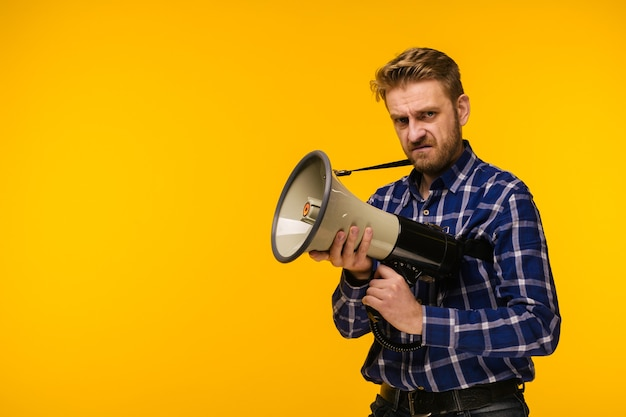 Young crazy mad man fool pose with a megaphone. announcement concept - image