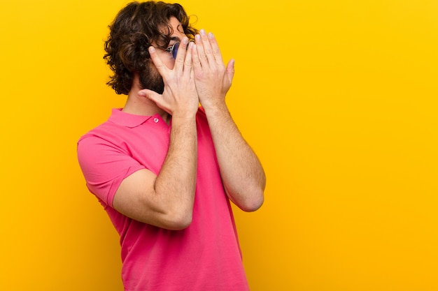 Young crazy man covering face with hands, peeking between fingers with surprised expression and looking to the side  orange wall