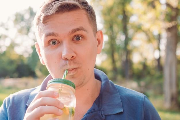 Молодой сумасшедший человек пьет мохито. мужчина на природе, погруженный в природу, выпивает стакан домашнего лимонада. витамины и концепция обычной жизни