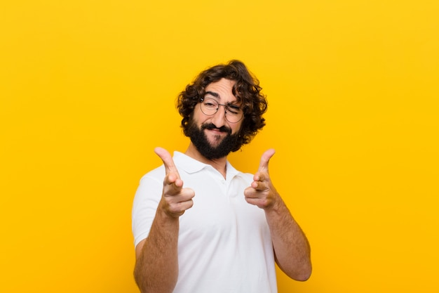 Young crazy man feeling happy, cool, satisfied, relaxed and successful, pointing at camera, choosing you  yellow wall
